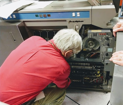 Frank King replacing a bad relay in the 1402 card reader. The relays are next to his right shoulder.