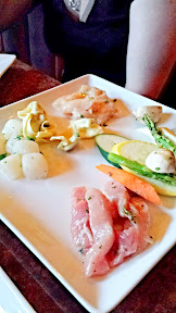 Urban Fondue, the broth courses with meats you cook. To the left you see the Chef's Cut entree with thin sliced Carlton pork and local New York strip loin seasoned with marjoram, extra virgin olive oil and spices, and the one to the right is the East Meets West entree with Carlton pork, local breast of chicken, east coast scallops and Tiger prawns.