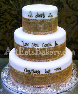Three tier white wedding cake with brown writing and burlap ribbons