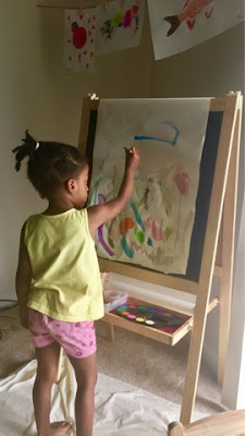 Childhood development milestones stay at home mom black brown girl painting easel toddler