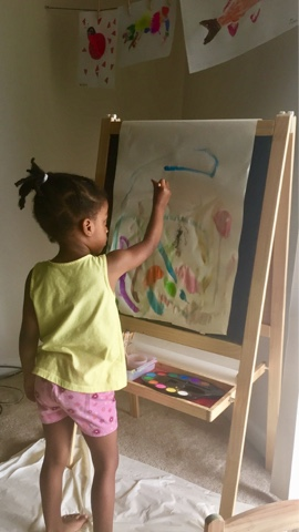 Childhood development milestones stay at home mom black brown girl painting easel toddler top mom mommy blogger