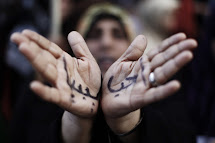 "A woman with the Arabic words for ""I love Libya"" written on her hands takes part in a rally supporting coalition air strikes in her country in the rebel-held city of Benghazi, March 23, 2011. REUTERS/Finbarr O'Reilly (LIBYA - Tags: CONFLICT CIVIL UNREST)"