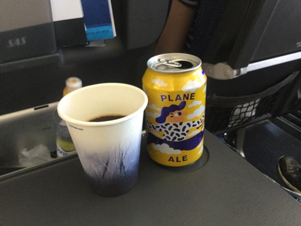 En kaffekopp og en ølboks på et flybord.