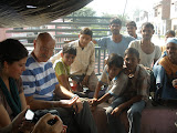 John, chair of the organisation that sponsored an eye camp, sits with a pv and villagers.