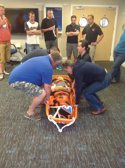Poole, Clovelly and Moelfre crew members preparing to lift Joe in a basket stretcher after he'd been immobilised with six fracture straps and collar. Trainer Grant Walkey looking on - July 2014 Photo: Dave Riley