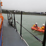Chris taking rowing tips from Dave while practising handling the daughter boat as part of their training. 6 April 2014 Photo: RNLI Poole/Anne Millman