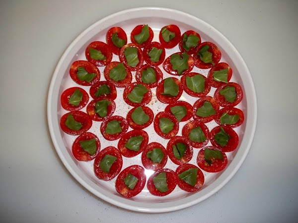 Tear basil leaves and press a piece down inside each tomato half.