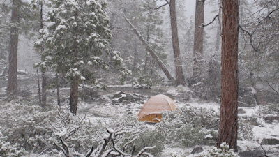 A beautiful scene...a warm tent, a down bag, and snow outside.©http://backpackthesierra.com