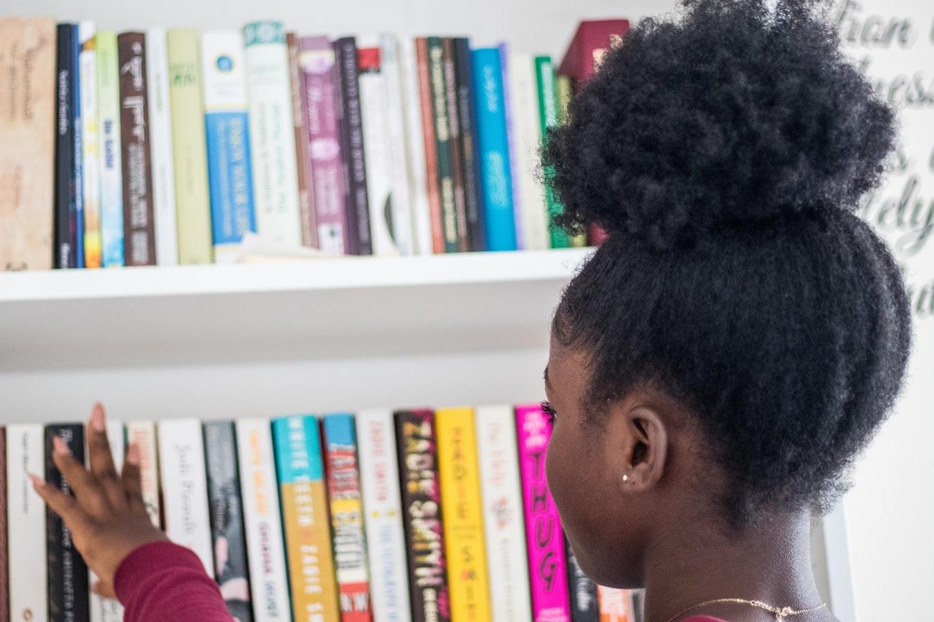 Uma garota pegando livro na estante