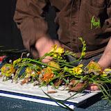 """Inspirat en el mestral que colpeja la seva terra, Gilles va fer un elegant centre de taula en tons grocs i verds on les flors """"s'inclienen"""" a un costat ajagudes pel vent."""