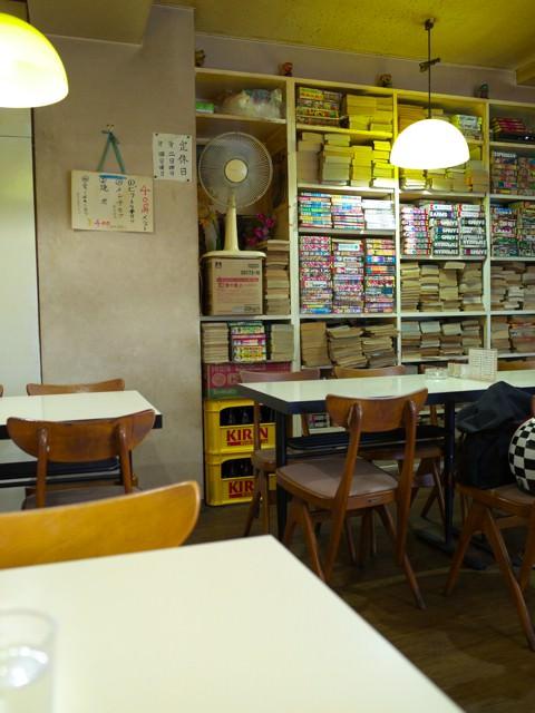 レストランテルの店内。テーブル席の奥にマンガ本コーナーがある。