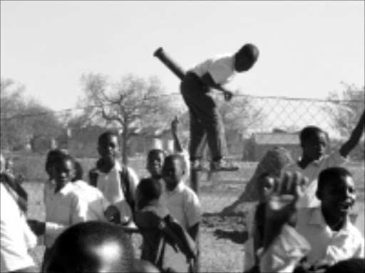 RUNNING SCARED: Pupils as young as seven years had to jump over the fence after scared teachers told them to run for thier lives because they thought a contractor was going to shoot them. Pic. Lazarus Mnisi. 23/09/2008. © Sowetan.