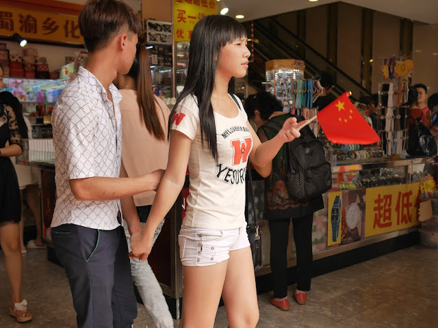 young woman holding a PRC flag in Zhongshan, China