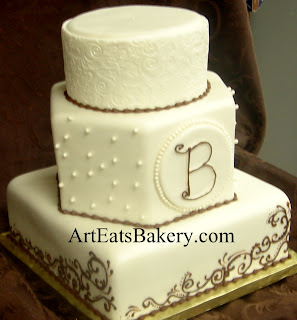 Three tier round, square and hexagon custom gold pearl fondant wedding cake with brown monogram, scroll piping and sugar pearls