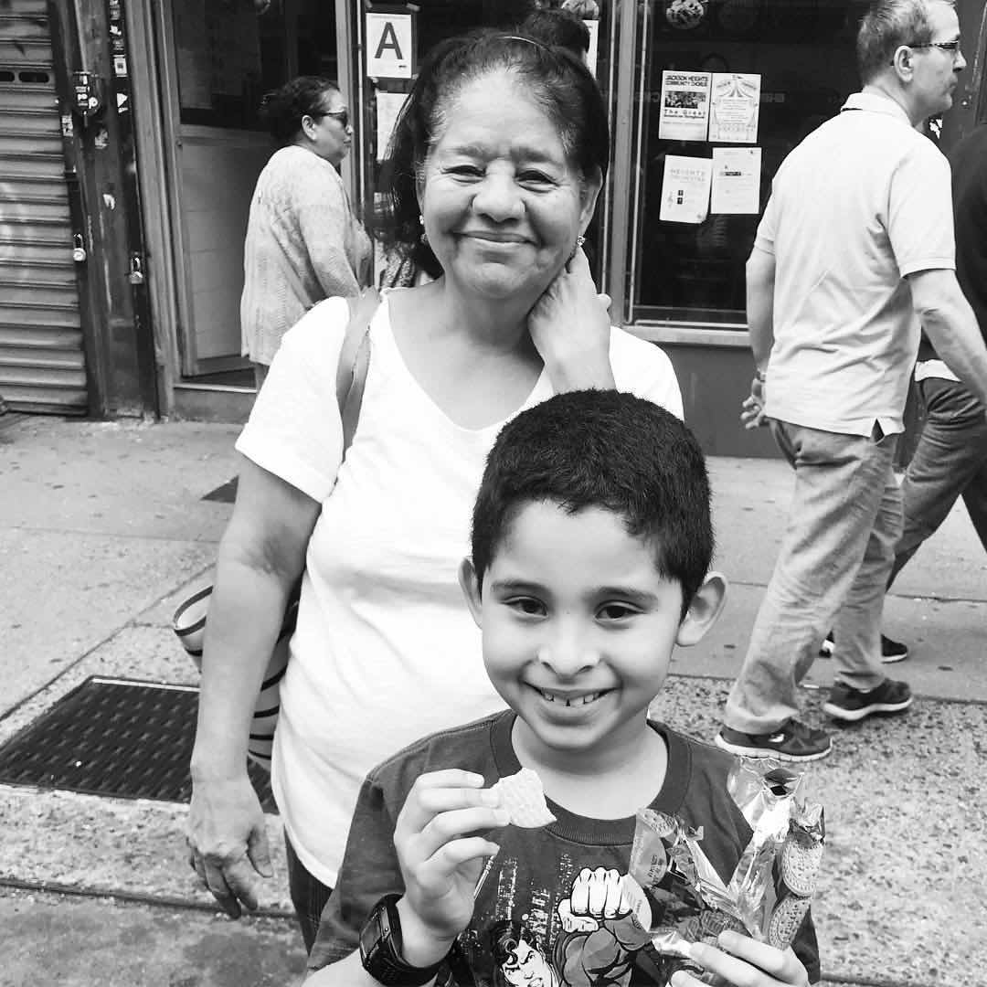 A mother and her son await the arrival of the Queens Pride parade in Jackson Heights.