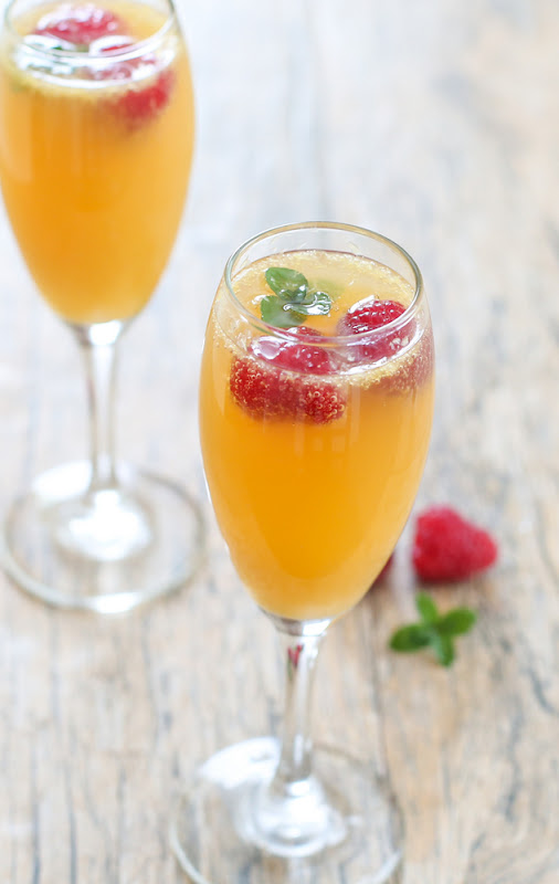 close-up shot of sweet tea mimosas garnished with fresh raspberries