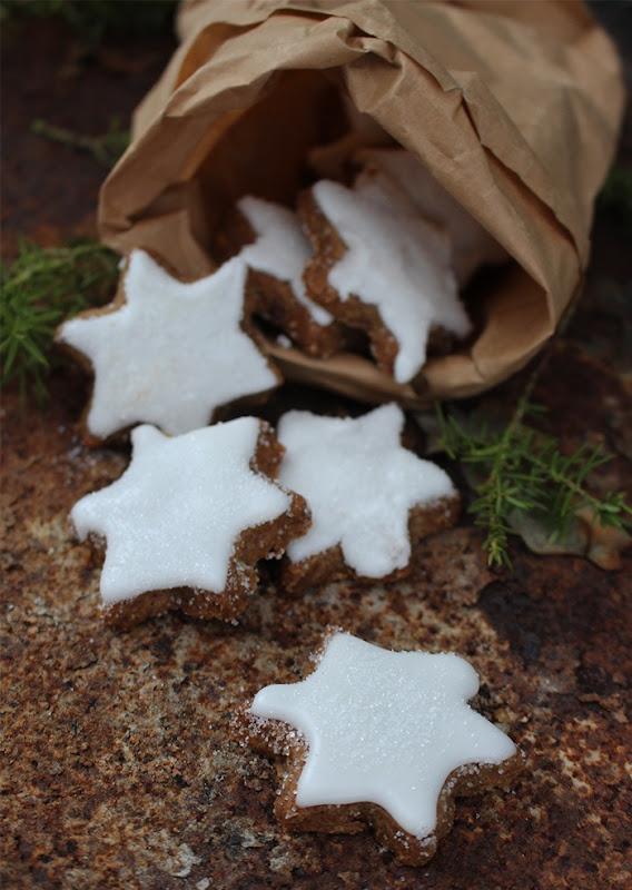En brun papperspåse fylld med bruna kakor i form av stjärnor dekorerade med glasyr.