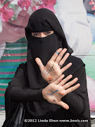 """My friend Zainab proudly shows off the writing on her hands: """"Our revolution is peaceful"""""""