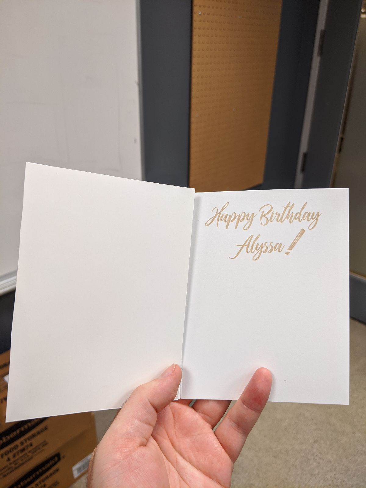"""Photo of the inside of the card, with """"Happy Birthday Alyssa!"""" laser etched. It looks like it's printed in tan ink"""