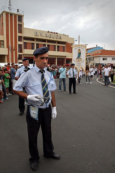 Trompetista em primeiro plano, em preno desfile. Como fundo, o quartel dos bombeiros e mais elementos da procissão