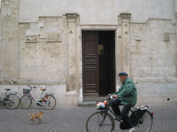 Church, cyclist and dog on Grosseto's shopping mile