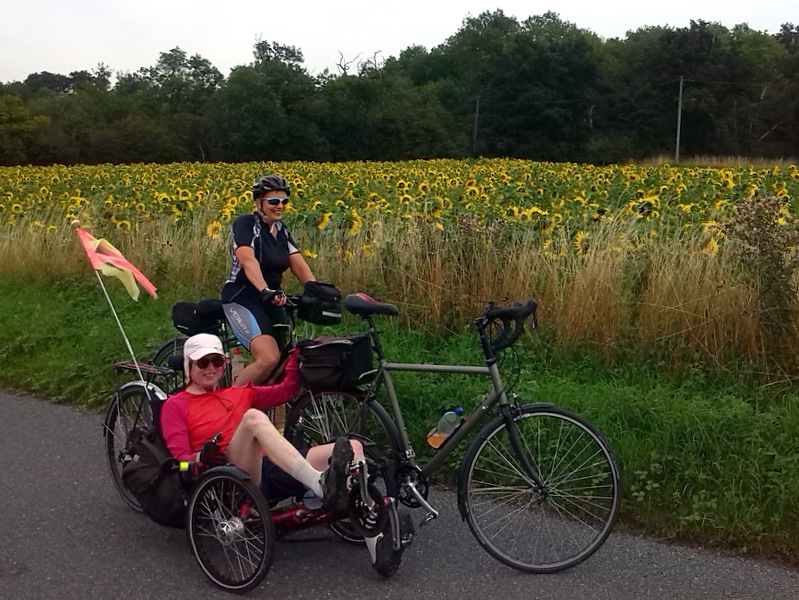Two female cyclists at a field of sunflowers
