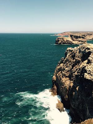 Utsikt mot en lang kystlinje med høye klipper.