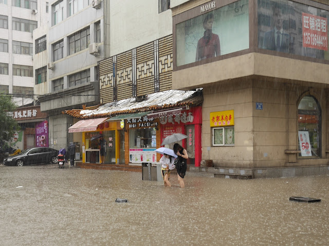 two young woman pulling up their skirts to avoid getting them wet on a flooded street in Taiyuan, China