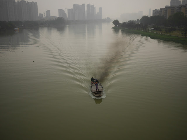 Man stands on a boat as it went down the Rongjiang North River in Jieyang, China