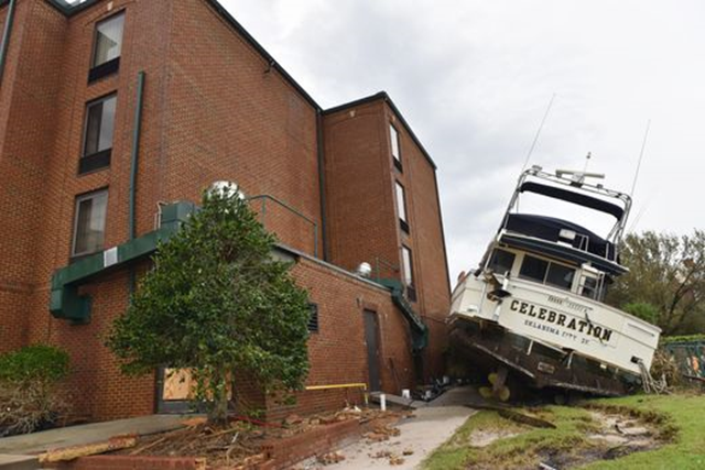 A yacht rests on the side of a downtown hotel in New Bern, N.C., Sunday, 16 September 2018. Hurricane Florence brought heavy rains and winds to the area. Photo: Tariq Zehawi / NorthJersey.com / USA TODAY