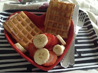 Red heart shaped dish with waffles, strawberries and sliced banana