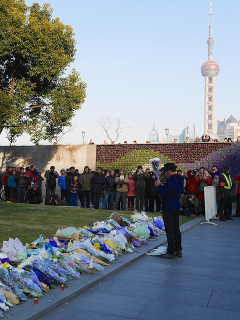 man praying while holding flowers in front of a memorial for people killed and injured by the New Year's Eve stampede in Shanghai