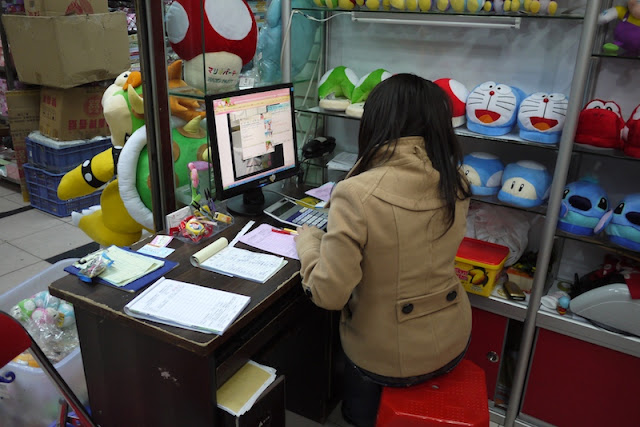 person on the phone and sitting at a computer in a small wholesale store in Guangzhou, Guangdong