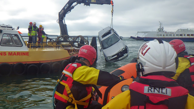Lifeboat and fire crew look on as the vehicle is raised above water - 27 October 2014.  Photo credit: RNLI/Poole