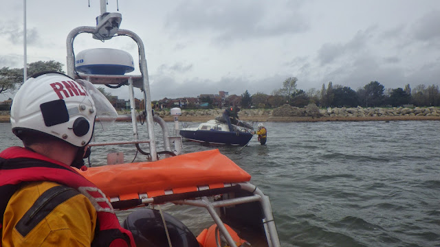 A volunteer crew member attaches a tow line to the grounded yacht - 17 October 2014.  Photo credit: RNLI/Poole