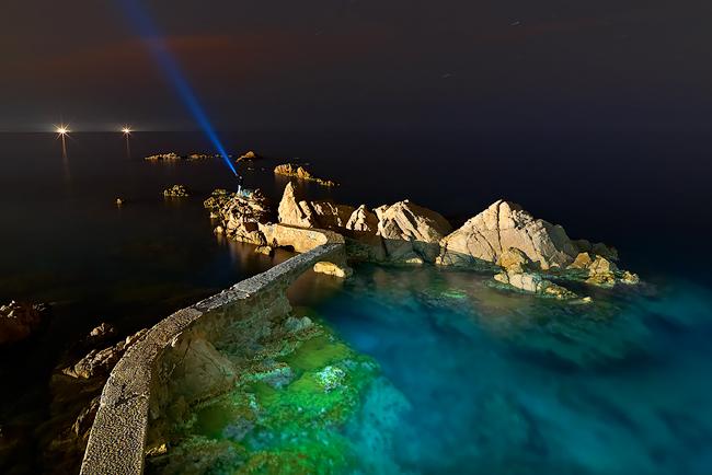 Imagen noctuna de un camino sobre la mar