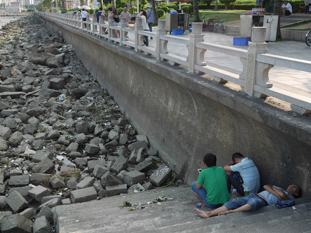 two men sitting and one sleeping on steps down to the water at Gongbei Harbor in Zhuhai