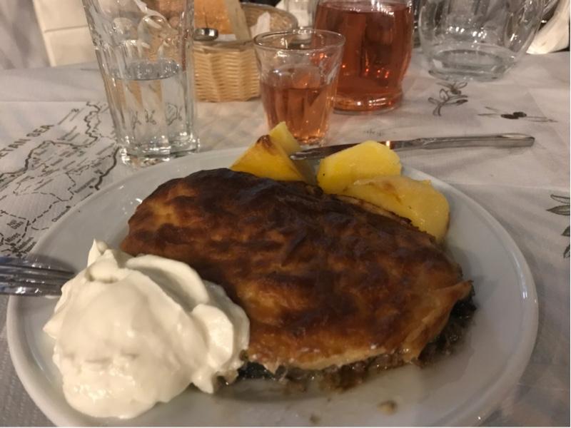 Et fat med moussaka, rømme og poteter. I bakgrunnen en kjøkkenglass med rosevin.