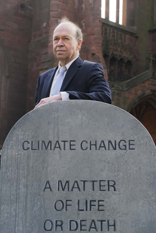 Climate scientist Dr. James Hansen stands behind a tombstone that reads, 'Climate change: A matter of life or death'. Photo: Arrizabalaga / REX Shutterstock