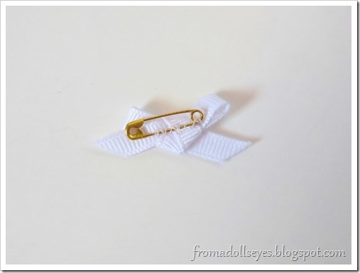 On the back of the bow is a tiny gold safety pin sewn on to make a doll sized bow pin.
