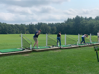 Corcoran Management Company employees swinging their clubs at the driving range at Kimball Farm