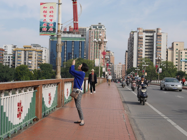 woman on a bridge photographing the sky in Shaoguan, Guangdong