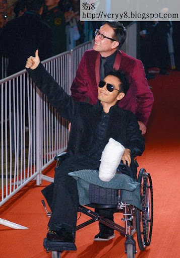 坐輪椅戴黑超嘅黃曉明由劉偉強推出紅地氈,十分搶鏡。