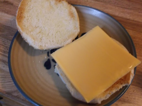 After toasting, place American cheese slice on one bun half.