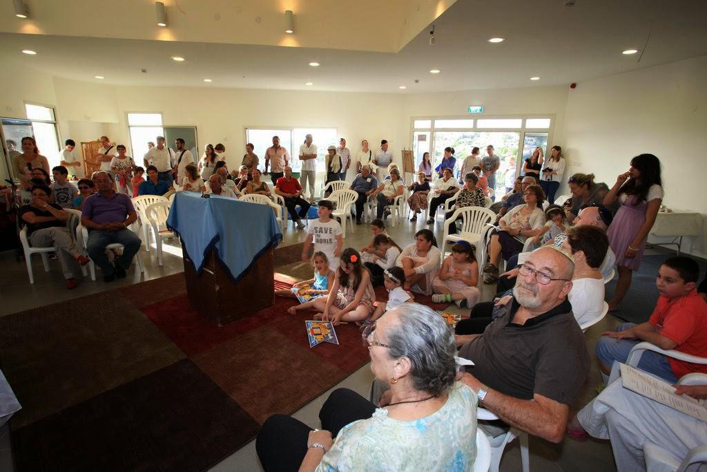 חברים ואורחים צופים בטקס שיכון ספרי התורה במשכנם החדש. Community members and guests at the ceremony of placing the Torah scrolls in their new home.