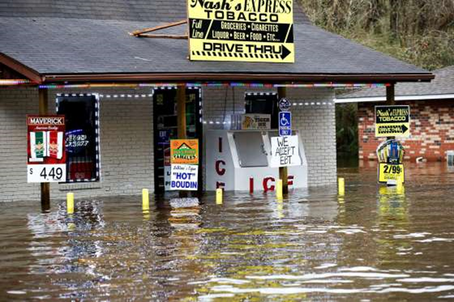 Flood waters rise against Nash's Express convenience store in Hammond, Louisiana, 11 March 2016. Torrential rains pounded northern Louisiana for fourth day Friday, trapping several hundred people in their homes, leaving scores of roads impassable and causing widespread flooding. Photo: Scott Threlkeld / AP Photo