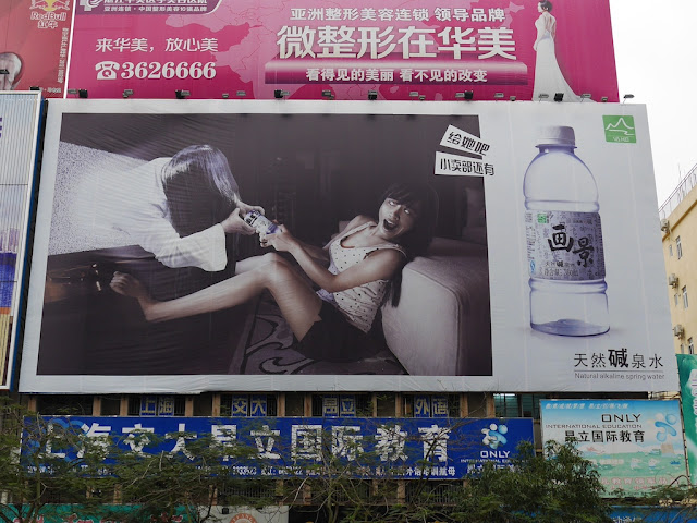 advertisement for Va Kin (画景) spring water including an image of a ghost woman coming out of a TV screen and trying to take away a bottle of water from a frightened woman