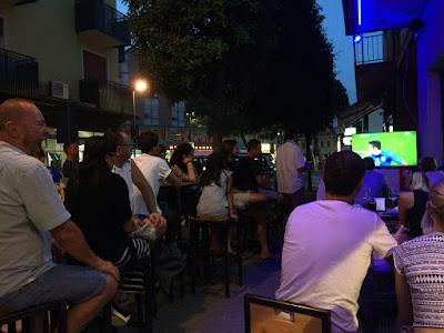 Flere mennesker som ser fotballkamp på TV utendørs om kvelden.