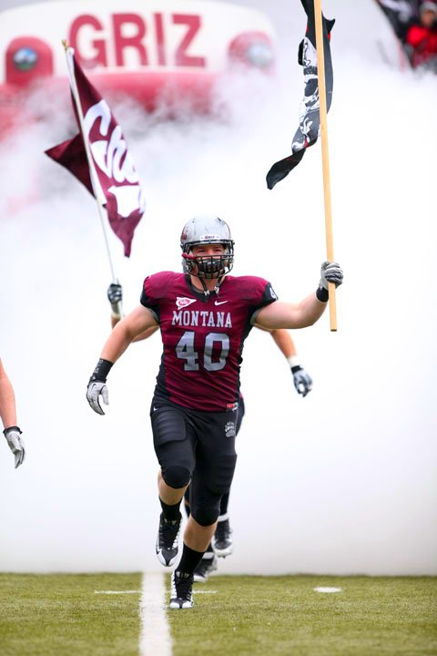 Caleb McSurdy leads the Grizzlies onto the field.