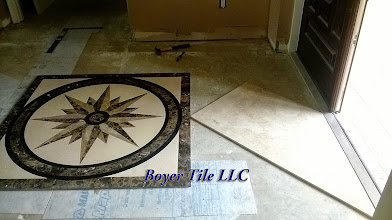 Photo: This custom inlay's position in this room will be the starting point for this installation. The other tile in this installation will be set on a diagonal, so the inlay's position has to be set to accommodate that layout. This looks right; Yes?